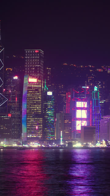 (vertical) timelapse of hong kong central district at waterfront in night time. - vertical format video stock videos and b-roll footage