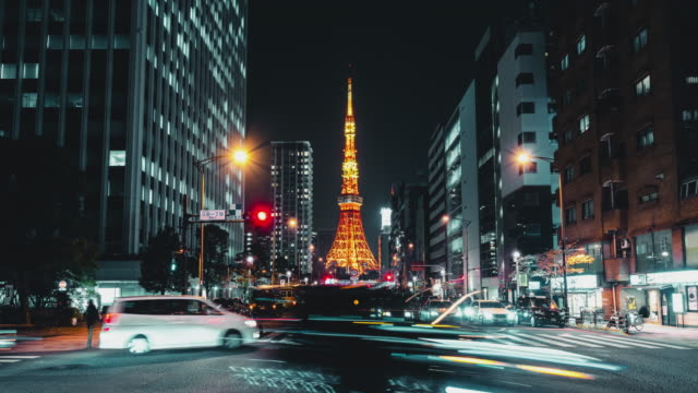 4k uhd time-lapse of illuminated tokyo tower, car traffic transport at night. japan landmark and transportation, tokyo tourist attraction, asian city life, or asia tourism concept. zoom in then still - segnale per macchine e pedoni video stock e b–roll