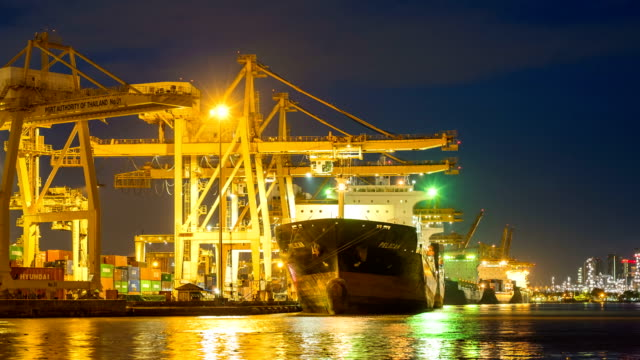 vídeos de stock e filmes b-roll de timelapse of industrial port with containers ship and cargo ship at night in south east asia - drone shipyard night