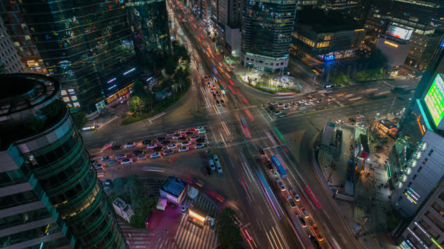 timelapse of light trails traffic speeds through an intersection in gangnam center business district of seoul at seoul city, south korea. - hyperlapse video stock e b–roll