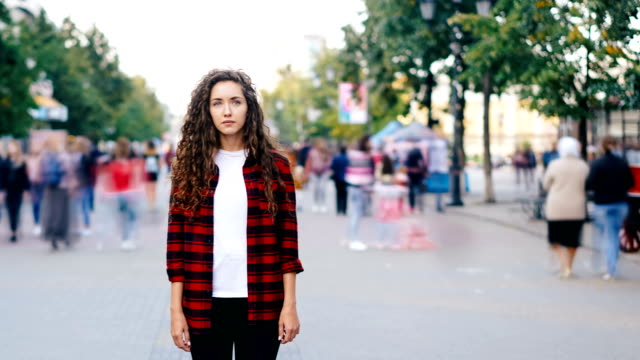 Time-lapse of lonely girl standing in city center on sidewalk looking at camera wearing casual clothing when crowd of people is moving around. Youth and life concept.