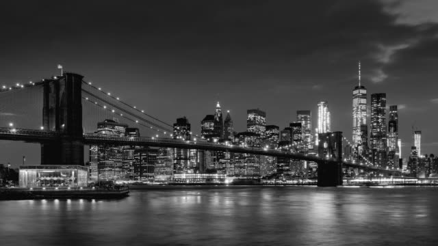Time-lapse of Lower Manhattan skyscrapers and Brooklyn Bridge with passing clouds at twilight in Black & White. Manhattan, New York City - vídeo