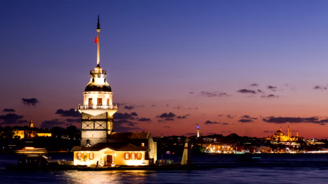Timelapse of Maiden Tower or Kiz Kulesi with floating tourist boats on Bosphorus in Istanbul at night video