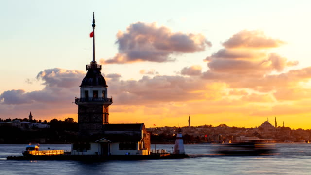 Timelapse of Maiden Tower or Kiz Kulesi with floating tourist boats on Bosphorus in Istanbul at sunset video