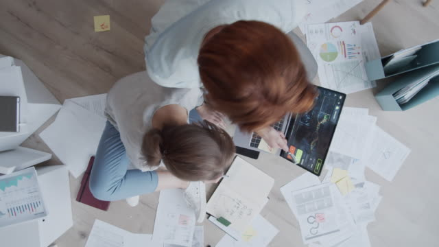 timelapse of man and woman sitting on floor, working with documents and diagrams - rude włosy filmów i materiałów b-roll