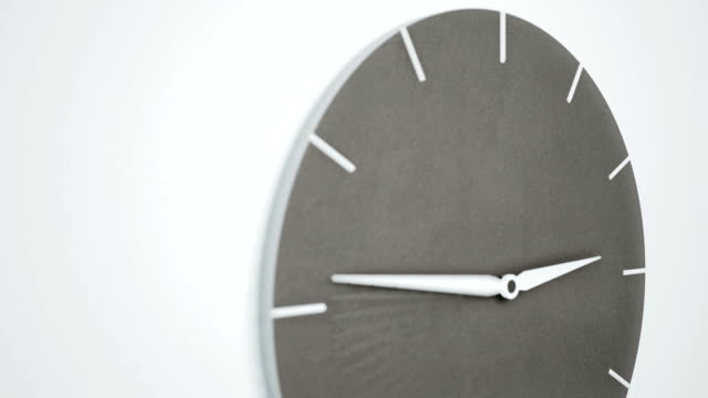 timelapse of modern minimalistic concrete clock on white wall. camera slides from top to bottom. - timeline filmów i materiałów b-roll
