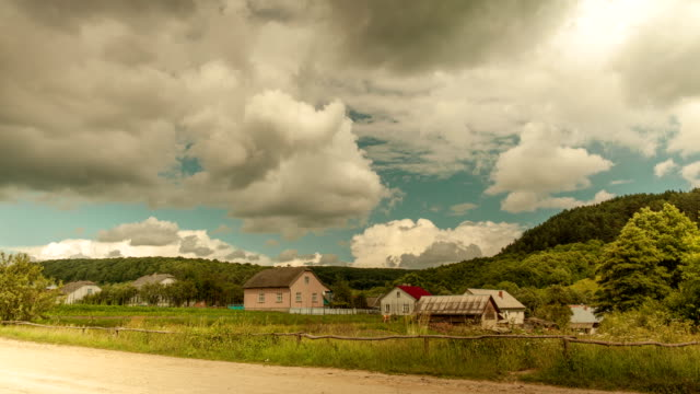 timelapse of moving clouds in village. - mandriano video stock e b–roll