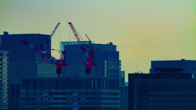 東京ロングショットの建物の上に移動クレーンのタイムラプス - クレーン点の映像素材/bロール