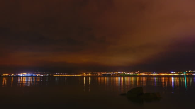 Timelapse of night city and sea. video