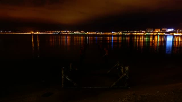Timelapse of night city and sea with old bridge. video
