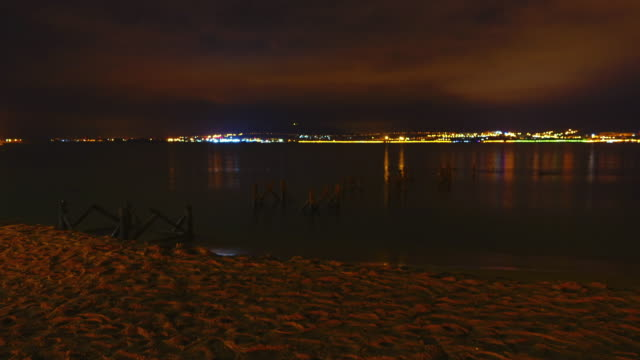 Timelapse of night city and sea with small waves. video