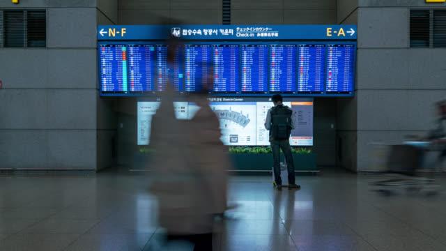 timelapse of people in international airport terminal, looking at information board, checking flight. - табло вылетов и прилётов стоковые видео и кадры b-roll