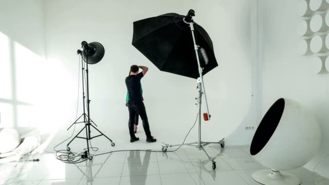 Timelapse of photographer and model working in studio Timelapse shot of professional photographer and woman model having photo shoot in studio photo shoot stock videos & royalty-free footage