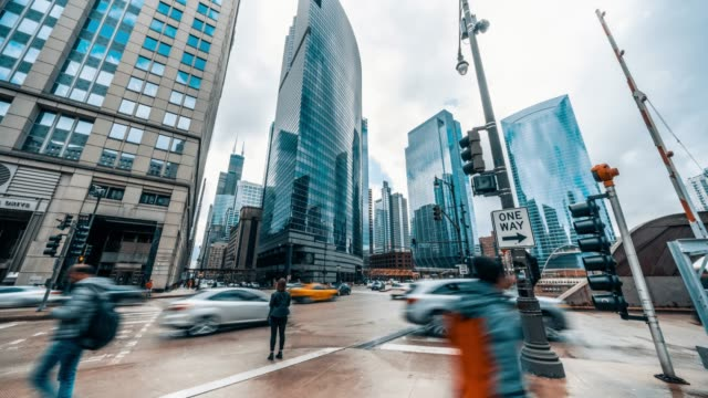 4K UHD time-lapse of road intersection in business district Chicago, USA. People walking and car traffic transport across streets. American city life concept