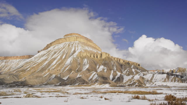 Timelapse of Rolling Clouds over the Striped, Eroded Sandstone Cliffs of the Bookcliffs (Geological Formation) and Mt. Garfield in the High Desert of Grand Junction and Palisade, Colorado on a Snowy Day