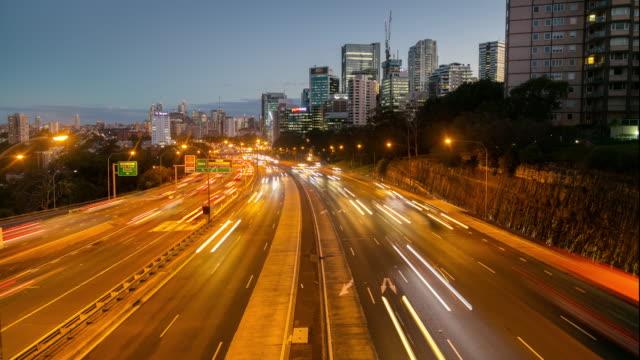 vídeos de stock, filmes e b-roll de tempo-lapso de 4k do tráfego da hora do rush - light trail