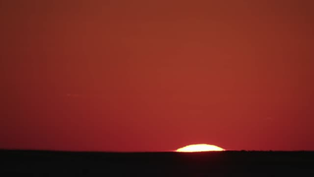 Time-lapse of sun rising against a beautiful red sky in the Makgadikgadi grasslands,Botswana Time-lapse of sun rising against a beautiful red sky in the Makgadikgadi grasslands,Botswana makgadikgadi pans national park stock videos & royalty-free footage