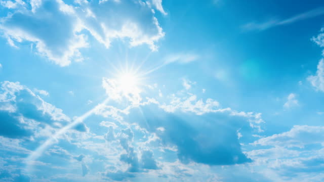 Time-lapse of sun shining bright on blue sky and clouds