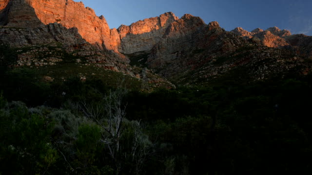Timelapse of sunset lighting up mountain in Du Toit's Kloof, South Africa, going to total darkness video