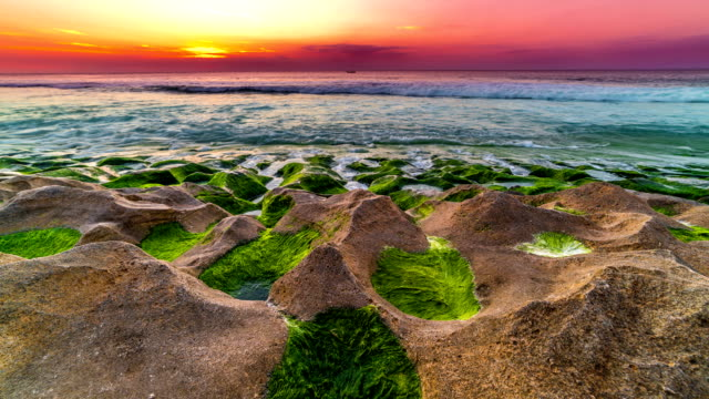 Timelapse of sunset on the Balangan beach with frozen volcanic funnels covered with algae on the island of Bali in Indonesia. video