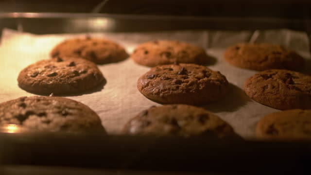Timelapse of the Chocolate Chip Cookies cooking process in 4K. A view through the oven door glass of melting and breaking Chocolate Chip Cookies in a fast speed. Preparing/cooking chocolate chip cookies step by step in 4K. cookie stock videos & royalty-free footage