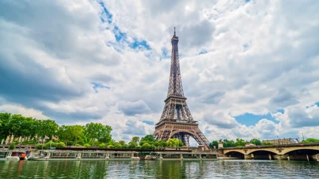vidéos et rushes de un timelapse de la tour eiffel le long de la seine avec des flyboats passant par le flou de mouvement. ensoleillé mais nuageux jour d'été paris ville célèbre tour de baie de bord vue panorama de timelapse de pont - paris