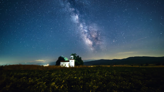 Timelapse of the night sky with stars and milky way over a small building during summer time.