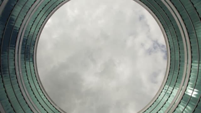 zeitraffer des himmels durch eine kreisförmige, loop-wie gebäude - kreis stock-videos und b-roll-filmmaterial