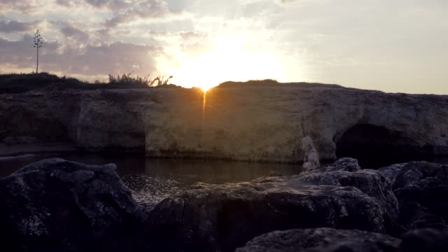 Timelapse of the sun rising behind the rocks at the Cirica Bay, Italy, 4K