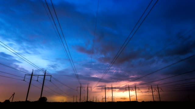 Time-lapse of thunderstorm, lightning and high voltage power lines. Time-lapse of thunderstorm, lightning and high voltage power lines. Power lines and five electricity pylons on a background of thunderstorm and lightning. Beautiful dramatic sky at dusk. Electricity theme. power supply stock videos & royalty-free footage