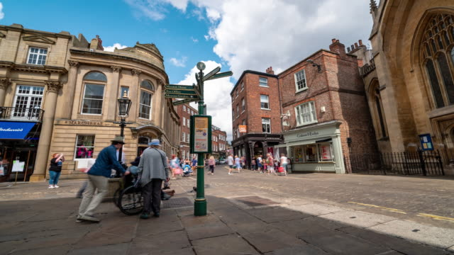 Time-lapse of Tourist Pedestrian crowded shopping street in York Yorkshire England UK.
