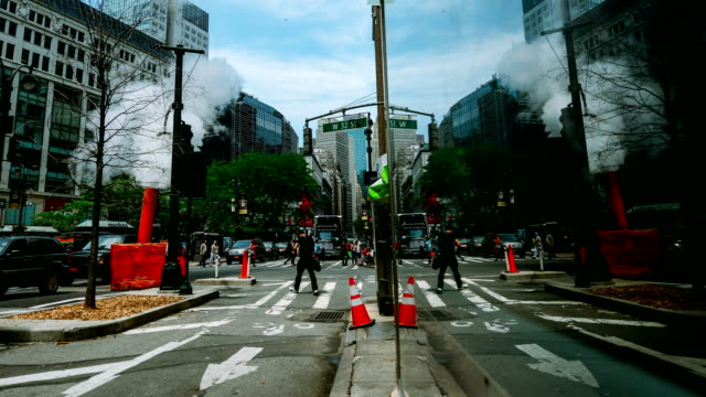 Timelapse of Traffic and pedestrians reflected on New York Building Timelapse of Traffic and pedestrians reflected on New York Building with steam coming from a manhole in midtown manhattan. double refraction stock videos & royalty-free footage