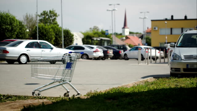 Timelapse of traffic on parking zone with empty shopping cart video