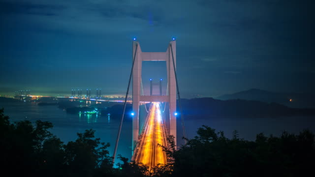 Time-lapse of traffic on the Seto Ohashi Bridge Time lapse of traffic and clouds at the Seto great bridge in the Seto inland sea. The bridge connects mainland Japan with the island of Shikoku. This is the view from Okayama looking out towards Sakaide, Kagawa.  suspension bridge stock videos & royalty-free footage