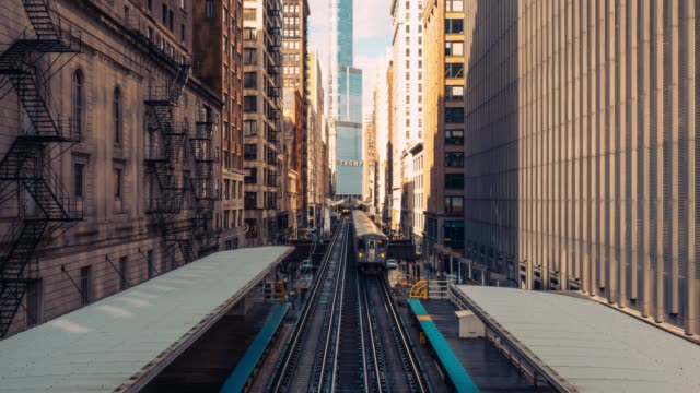 4k uhd time-lapse of trains arriving railway station between buildings in downtown chicago, illinois. urban public transportation, usa landmark, or american midwest city life concept - tor kolejowy filmów i materiałów b-roll