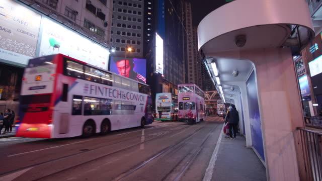 time-lapse av spårvagnen posterar i nattetid på causeway fjärden, hong kong. - billboard train station bildbanksvideor och videomaterial från bakom kulisserna