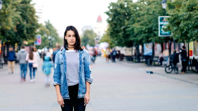 time-lapse of unhappy lonely girl standing alone in the street and looking at camera when people are walking around fast. loneliness and modern life concept. - solitario video stock e b–roll