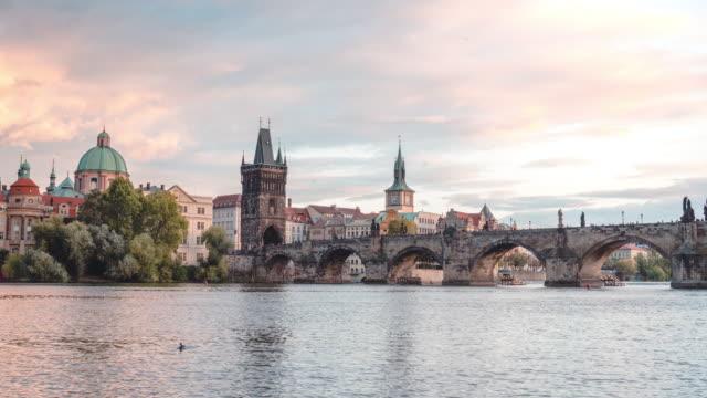 timelapse of vltava river and charles bridge in sunset in prague - barocco video stock e b–roll