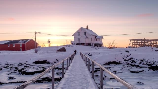 zeitraffer des weißen hauses mit holzbrücke und gefrorenen küste bei sonnenaufgang am morgen - schneeflocke sonnenaufgang stock-videos und b-roll-filmmaterial