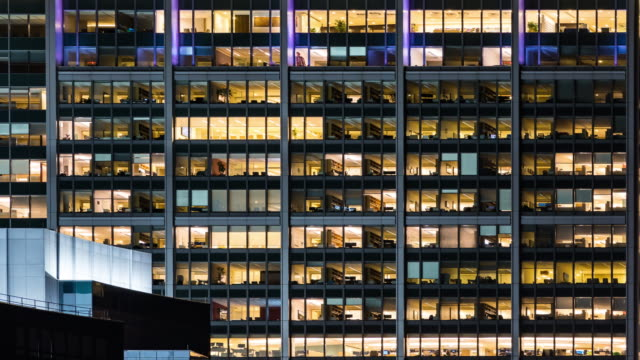 time-lapse office window night in boston city usa for late working concept - edificio adibito a uffici video stock e b–roll