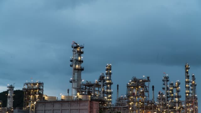Time-lapse oil refinery day to night with storm clouds.