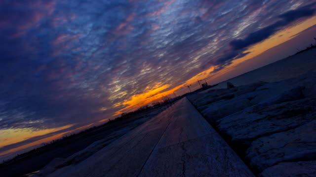 vídeos de stock e filmes b-roll de timelapse on the sea dike at sunset in the evening - barragem do roxo