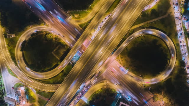 Time-lapse or Hyper-lapse Aerial top view highway road roundabout circle or intersection traffic at night for transportation.