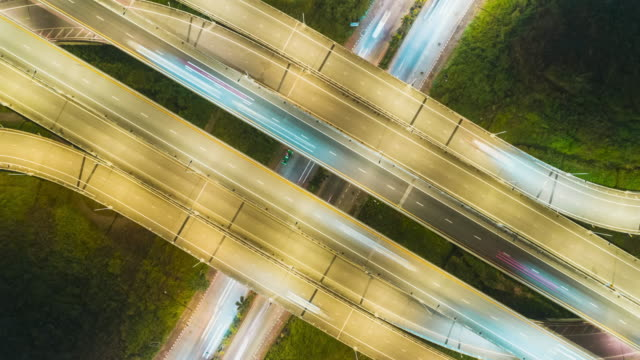 Time-lapse or Hyper-lapse Aerial view highway road intersection traffic at night for transportation concept.