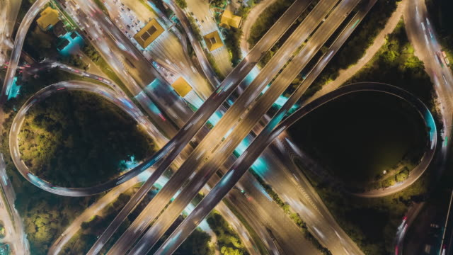 Time-lapse or Hyper-lapse Aerial view highway road roundabout circle or intersection traffic at night for transportation concept.
