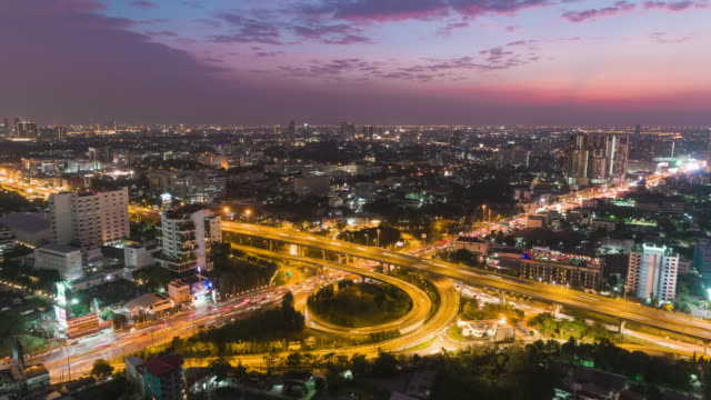 Time-lapse or Hyper-lapse Aerial view highway road roundabout circle or intersection traffic with cityscape at dusk for transportation.