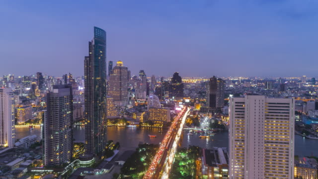 Time-lapse or Hyper-lapse Aerial view highway road traffic and cityscape at dusk for transportation.