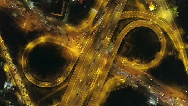 Time-lapse or Hyper-lapse zoom in : Aerial top view highway road roundabout circle or intersection traffic at night for transportation.