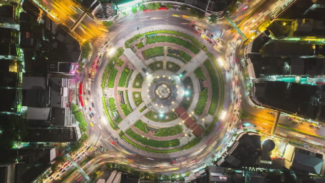 Time-lapse or Hyper-lapse Zoom in Aerial view 4 way road roundabout circle or intersection traffic at night for transportation concept.