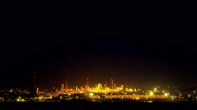 4K Timelapse. Panorama of a glowing refinery at night, like a background video